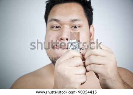 Fat man with chocolate - stock photo