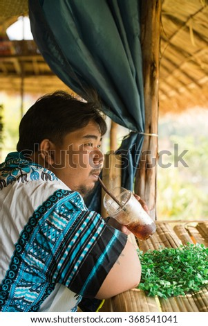 Fat man with coffee watching a mountain view , Thailand. - stock photo