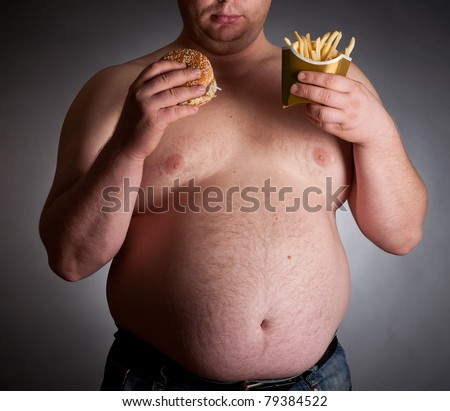Fat man with hamburger and chips on dark background - stock photo