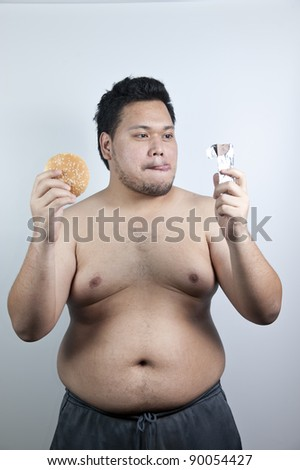 Fat man with hamburger and chocolate - stock photo