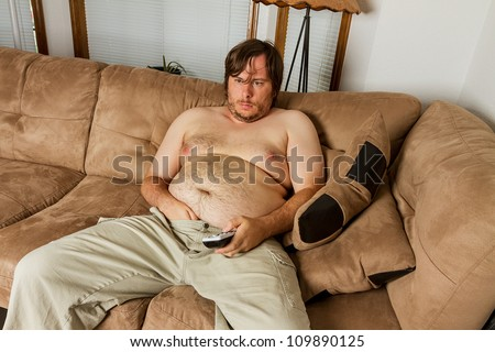 Fat obese man  on the couch with remote in one hand and the other hand shoved down the front of his pants. Shows obesity due to lack of exercise. - stock photo