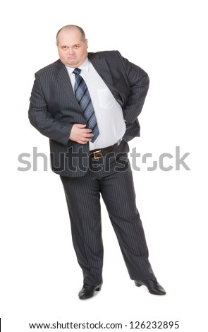 Fat overweight businessman in a stylish suit standing with his hand on his hip glowering at the camera with a displeased expression, studio portrait on white - stock photo