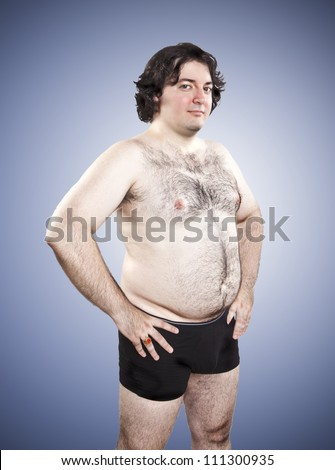 fat proud young man on blue background - stock photo