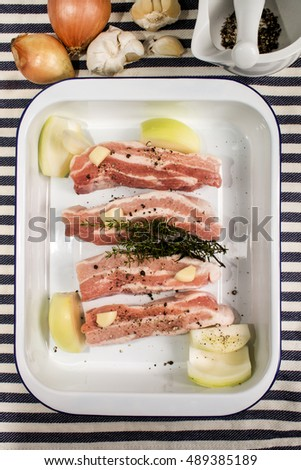 fat raw pork belly with onion, garlic, crushed black peppercorn and thyme in an enamel roasting tin