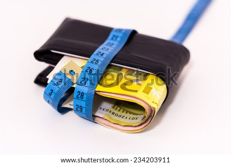 Fat wallet with a measuring tape - stock photo
