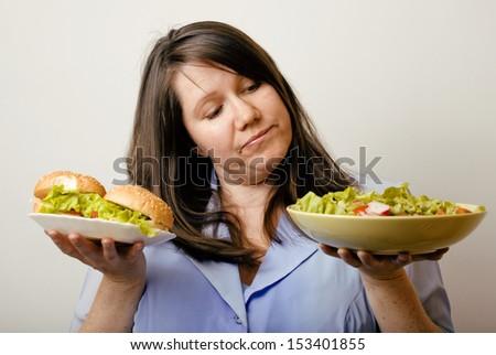 fat white woman having choice between hamburger and salad - stock photo