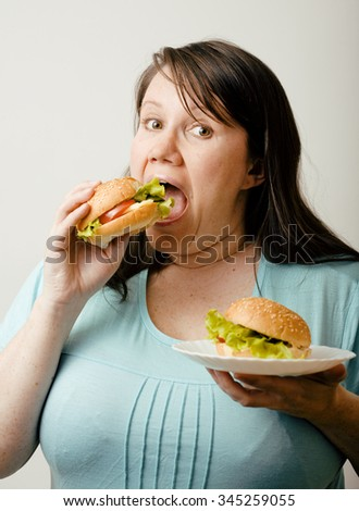 fat white woman having choice between hamburger and salad emotional