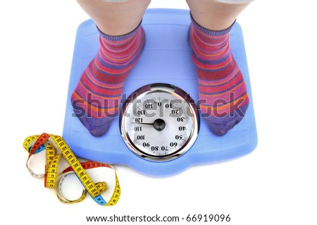 Fat woman body part in a scale and a measuring tape - stock photo