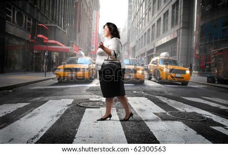 Fat woman crossing a city street - stock photo