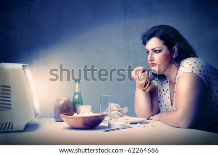 Fat woman dining in front of the television - stock photo