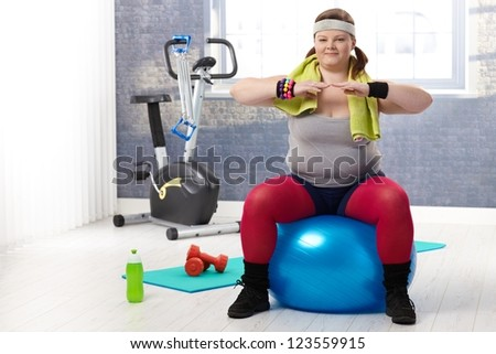 Fat woman doing gymnastics, sitting on fit ball at the gym. - stock photo