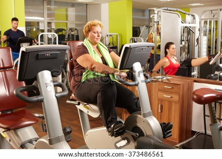 Fat woman doing workout on exercise bike in gym. - stock photo