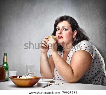 Fat woman feeling guilty while eating junk food - stock photo