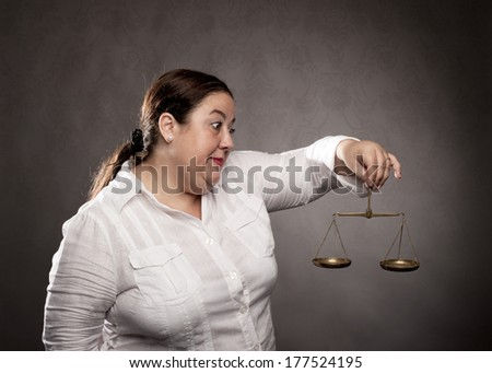 fat woman holding a scale on a gray background - stock photo