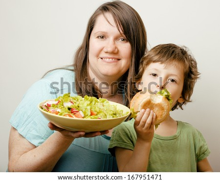 fat woman holding salad and little cute boy with hamburger teasing - stock photo