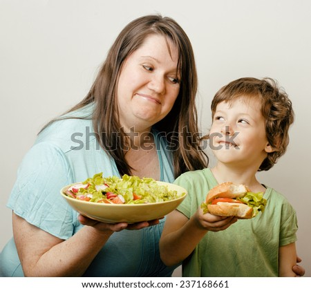 fat woman holding salad and little cute boy with hamburger teasing, real family scene.