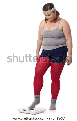 Fat woman in sportswear stepping on scale with fear. - stock photo
