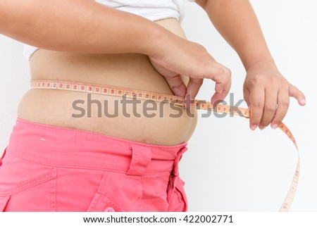 Fat woman measuring her belly with measurement tape
