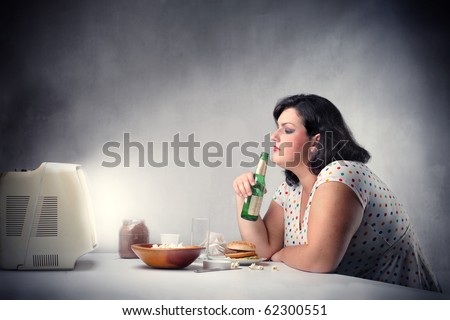 Fat woman sitting in front of the television and drinking a beer - stock photo