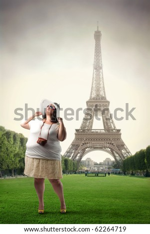 Fat woman standing in front of the Eiffel Tower - stock photo
