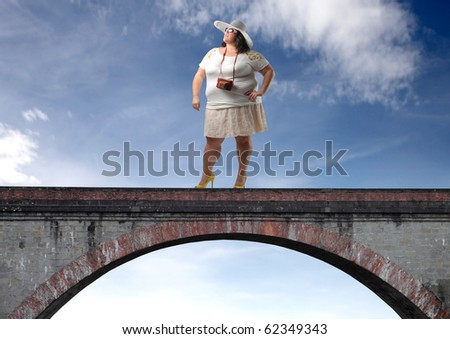 Fat woman standing on a bridge - stock photo