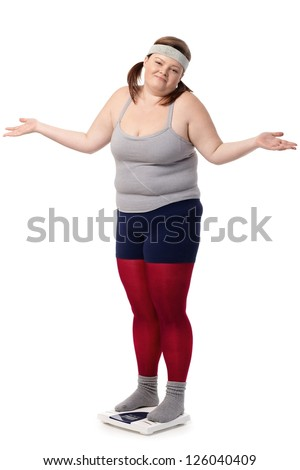 Fat woman standing on scale disappointed with opened arms, wearing sportswear. - stock photo