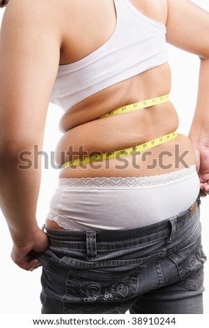 Fat woman trying to wear tight jeans from backside with measuring tape around her belly