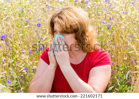 Fat woman with allergic rhinitis in the meadow - stock photo