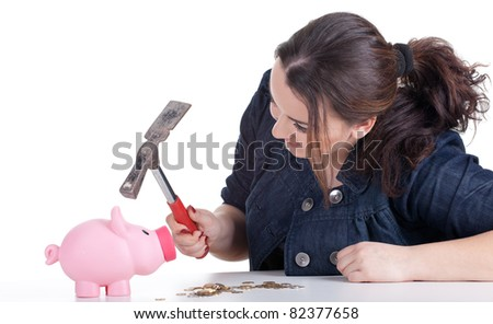 fat young woman trying to broke pink piggy bank - stock photo