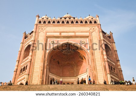 Fatehpur Sikri, India - January 9, 2015 : People in front of the facade of the main entrance of the Jama Masjid, the Mughal mosque in Fatehpur Sikri near Agra in India - stock photo