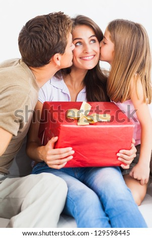 Fathe rand his daughter offering a gift and kissing - stock photo