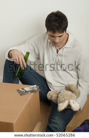 Father alone, just moved into his new house, missing his little boy - stock photo