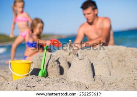 Father and adorable little daughter playing with beach toys during tropical vacation - stock photo