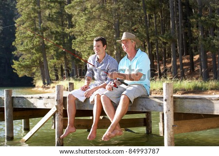 Father and adult son fishing together - stock photo