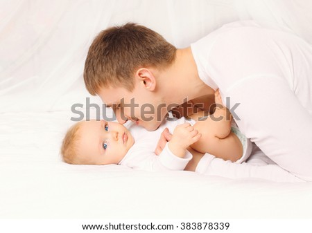 Father and baby at home lying on the bed together bedtime - stock photo