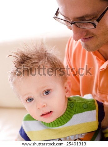 Father and baby boy enjoy time together at home. - stock photo
