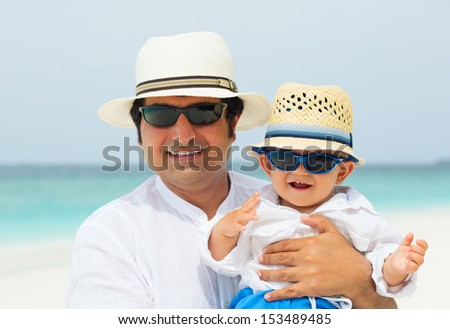 Father and baby boy having tropical vacation on Maldives. Standing with panama hats and sunglasses on the beach. Close up portrait.  - stock photo