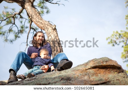 Father and baby boy in nature under a pine tree on cliffs, shallow DOF, child in focus