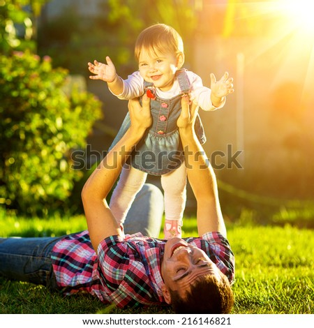 Father and baby daughter are playing outdoors. Young daddy and his cute little baby-girl are having fun in the sunny garden. Happy childhood and parenthood concept. Focus on the daughter. - stock photo
