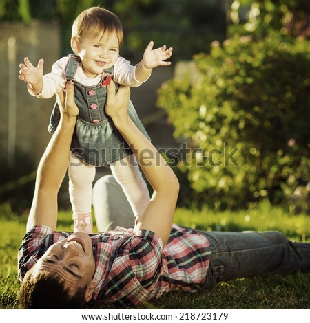 Father and baby daughter are playing outdoors. Young daddy and his cute little baby-girl are having fun in the sunny garden. Happy childhood and parenthood concept. Focus on the daughter. Instagram  - stock photo