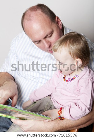 Father and baby daughter reading a picture book