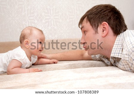 Father and baby daughter, talking, smiling,  lying on the bed and looking eye to eye with each other. - stock photo