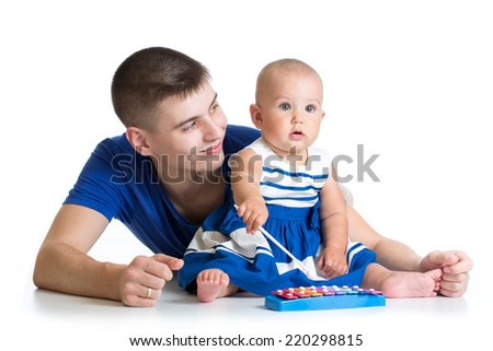 Father and baby girl having fun with musical toys. Isolated on white background - stock photo