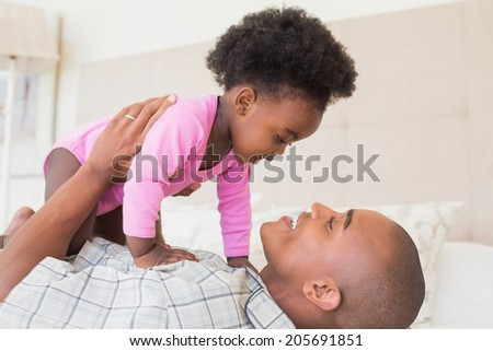Father and baby girl lying on bed together at home in the bedroom - stock photo
