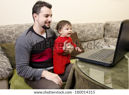 Father and baby looking pc at home living room - stock photo
