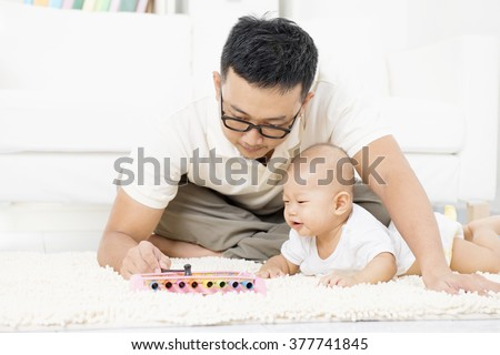 Father and baby playing music instrument. Sound development concept. Asian family lifestyle at home. - stock photo