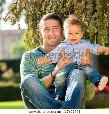 father and baby playing on the grass - stock photo