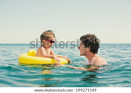 father and baby son playing in sea water - stock photo