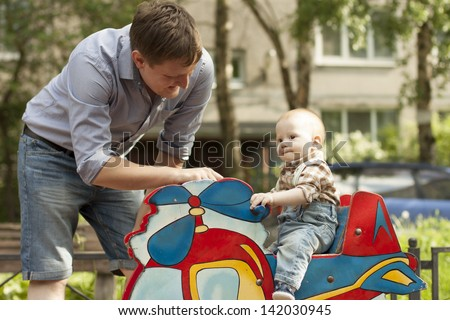 Father and baby son playing on the swings at playground - stock photo