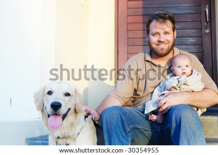 father and baby son sitting with their dog on the porch in the evening sun, focus on the father - stock photo